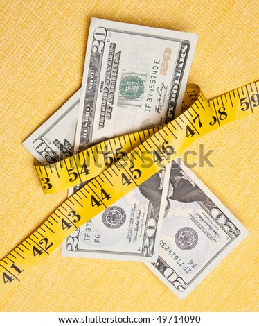 American currency is squeezed by a yellow measuring tape on a measuring background to demonstrate that money is tight. - stock photo