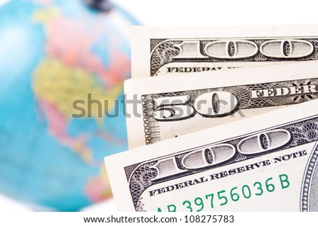 American Dollar-bills and blurred earth-globe in the background - stock photo