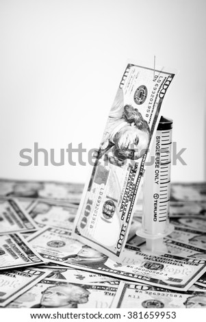 American dollars with syringe costs for the medical insurance,Focus on eye of 100 dollar with black and white color - stock photo