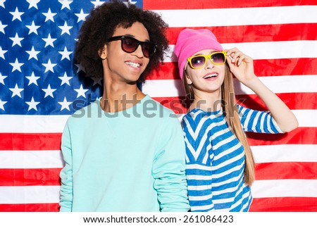 American dreams. Funky young couple wearing sunglasses and smiling while standing against American flag - stock photo