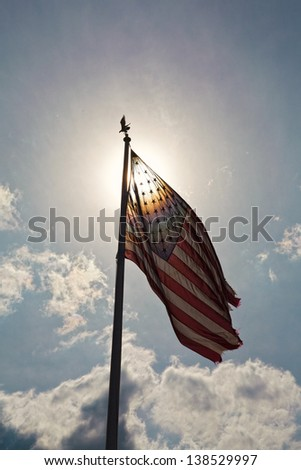 American flag against a blue cloudy sky. - stock photo