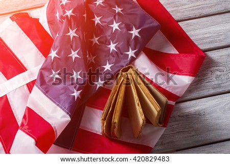 American flag and old book. Flag and book under sunlight. Rights and freedoms of nation. History, culture and traditions. - stock photo