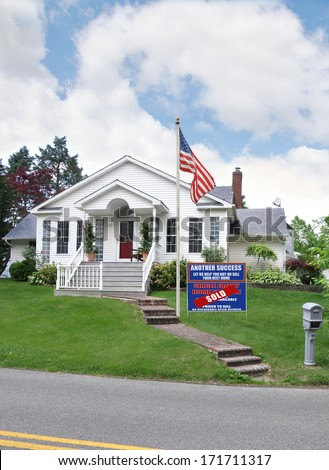 American Flag and Sold real estate sign (another success let us help you buy sell your next home) suburban home residential neighborhood USA blue sky clouds - stock photo