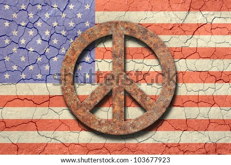 American flag background with an arid cracking soil appearance. Up front a rusty peace sign./ Cracking American Flag, Rusty Peace Symbol /  Great look, with a straightforward point of view. - stock photo