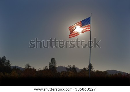 American flag blowing in the wind backlit by the sun with slight halo                                - stock photo