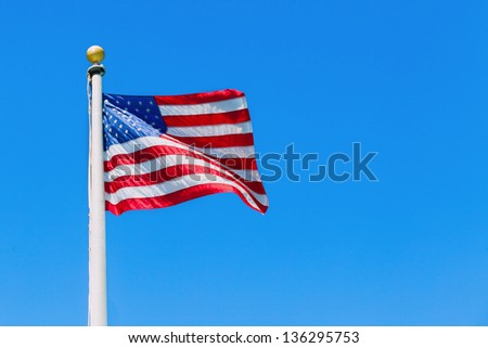 American flag flying in the wind on a flagpole with a brass ball finial - stock photo