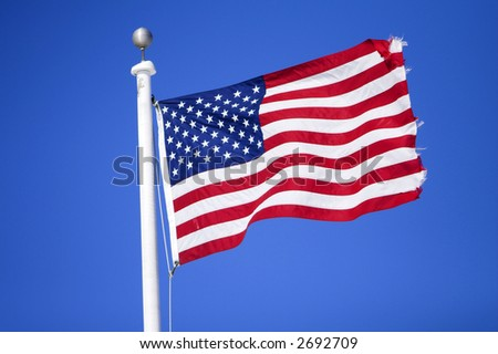 American flag flying over a blue background - stock photo