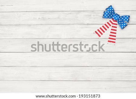 American Flag Glitter Bow in Upper Right Corner on worn Rustic Painted White Wood Board Background with room or space for copy, text.   Horizontal - stock photo