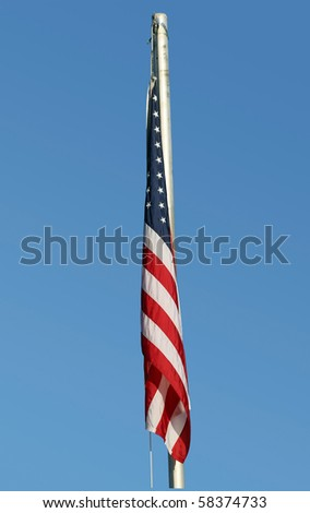 American flag hanging limply on calm, peaceful day with clear blue sky. - stock photo