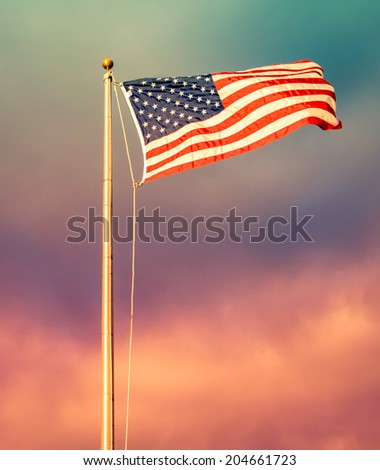 American flag in foreground, waving and brightly lit with rising sun's golden sunlight and ominous clouds in the background, with instagram style retro processing - stock photo