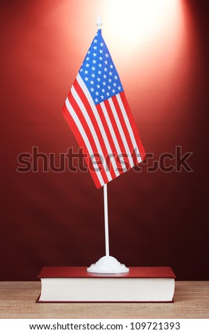 American flag on the stand and book on wooden table on red background - stock photo