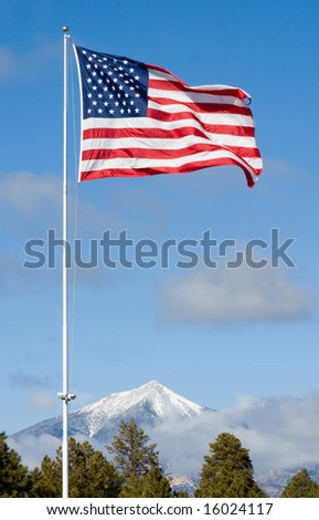 American Flag over Snow Capped Peaks - stock photo