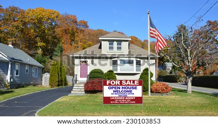 American Flag pole and Real Estate For Sale Open House Welcome sign on front yard lawn of suburban bungalow style home residential neighborhood clear blue sky USA - stock photo