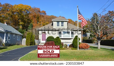 American Flag pole and Sold Real Estate (another success let us help you buy sell your next home) sign on front yard lawn of suburban bungalow style home residential neighborhood clear blue sky USA - stock photo