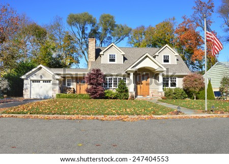 American flag pole beautiful suburban cape cod style home autumn clear blue sky day residential neighborhood USA - stock photo