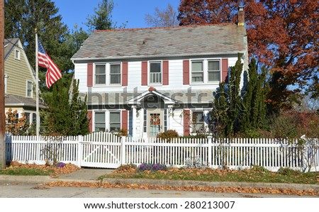 American flag pole Beautiful Suburban Colonial Home with white picket fence autumn clear blue sky day residential neighborhood USA - stock photo