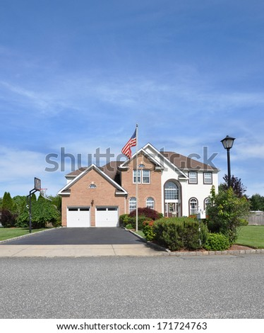 American Flag pole front yard lawn of Suburban McMansion style brick home Landscaped sunny residential neighborhood USA blue sky clouds - stock photo