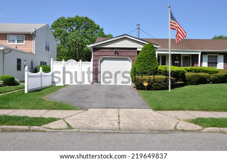 American flag pole on front yard lawn suburban home residential neighborhood USA clear blue sky - stock photo
