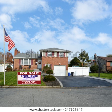 American flag pole Real estate for sale open house welcome sign Beautiful Suburban Brick Snout style home landscaped yard residential neighborhood USA blue sky clouds - stock photo