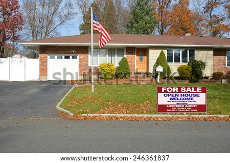 American flag pole Real estate for sale open house welcome sign suburban brick ranch style home white picket fence blacktop driveway autumn blue sky day residential neighborhood USA - stock photo
