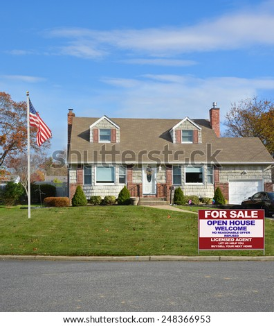 American flag pole Real estate for sale open house welcome sign Suburban Cape Cod home landscaped beautiful autumn day residential neighborhood USA - stock photo
