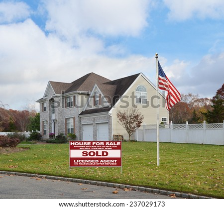 American flag pole Real Estate sold (another success let us help you buy sell your next home) sign Suburban brick McMansion home with two car garage white picket fence residential neighborhood USA - stock photo