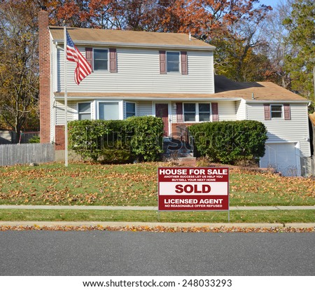 American flag pole Real estate sold (another success let us help you buy sell your next home) sign Suburban Tan High Ranch home with leaves on front lawn autumn day residential neighborhood blue sky - stock photo