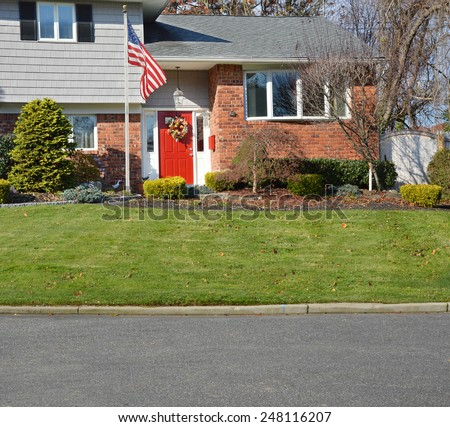 American flag pole suburban brick high ranch home sunny residential neighborhood USA - stock photo