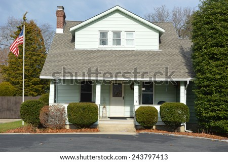 American flag pole Suburban Bungalow style home with blacktop driveway residential neighborhood USA - stock photo