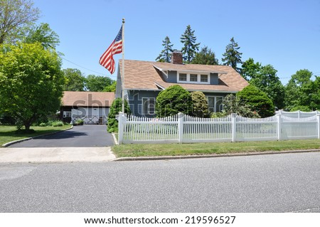 American Flag Pole Suburban cape cod style home with white picket fence residential neighborhood clear blue sky USA - stock photo