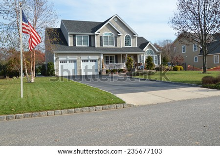 American flag pole Suburban McMansion home autumn day residential neighborhood USA - stock photo