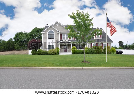 American Flag Pole Suburban McMansion Home Residential Neighborhood USA Blue Sky Clouds - stock photo