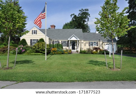 American Flag pole suburban ranch style home landscaped flowers plants trees sunny blue sky day residential neighborhood usa  - stock photo