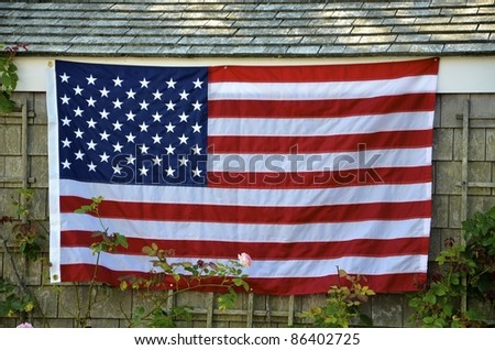 American flag proudly displayed on the side of a shingled house. - stock photo