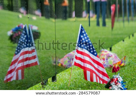 American Flag sits next to a traveling Vietnam memorial wall with the flags reflection. - stock photo