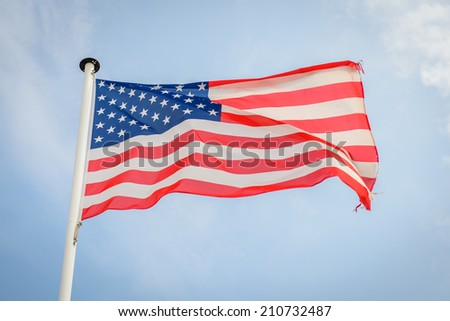 American flag waving against blue sky - stock photo