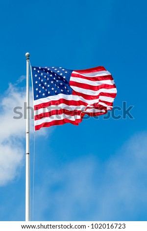 American flag waving against blue sky with room for text. - stock photo