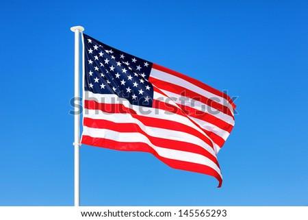 American flag waving in blue sky - stock photo