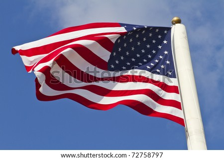 american flag waving in the wind, focus set on the Stars. - stock photo