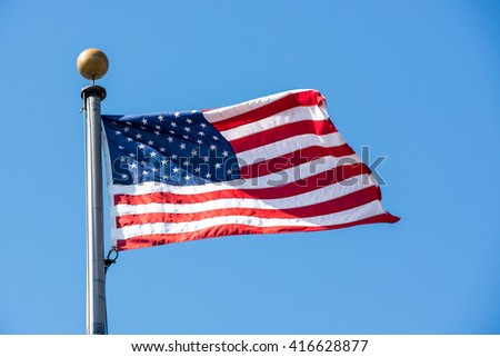 American flag waving with the wind on a clear blue sky. - stock photo