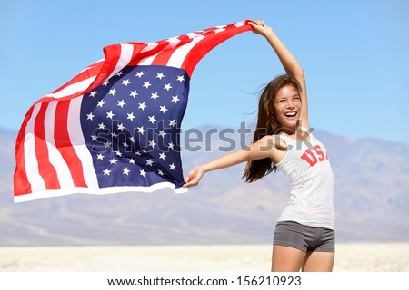 American flag - woman USA sport athlete winner cheering waving stars and stripes outdoor after in desert nature. Beautiful cheering happy young multicultural girl joyful and excited. - stock photo