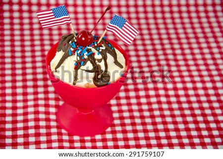 American flags in a hot fudge sundae with sprinkles on red and white checkered tablecloth - stock photo
