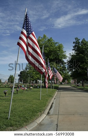 American flags lining street through cemetery with cloud streaked blue sky in background. - stock photo