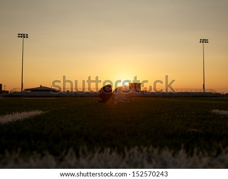 American Football and Helmet on the Field at Sunset with Stands Beyond - stock photo