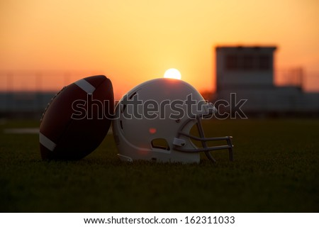 American Football and Helmet on the Field Backlit at Sunset with Sun glare for effect - stock photo