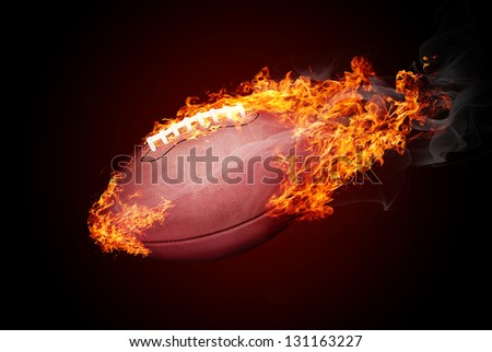 American football ball in fire isolated on dark red background - flying down - stock photo