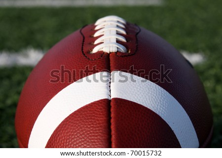 American Football close up with yard lines beyond - stock photo