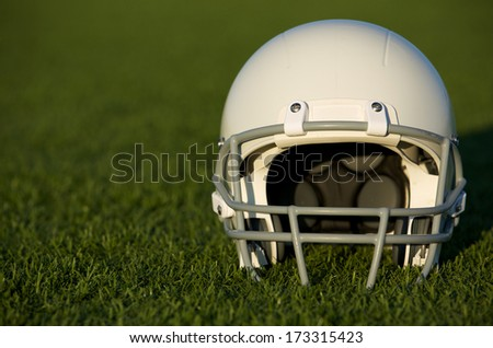 American Football Helmet on the Field with room for copy - stock photo