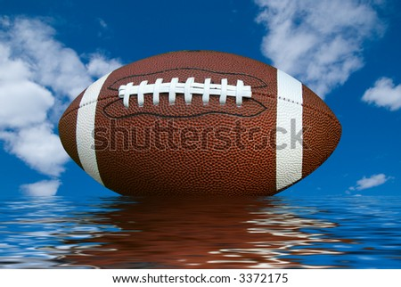 American football isolated over a cloudy sky background with water reflection - stock photo