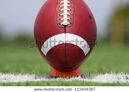 American Football on a Tee ready for kickoff - stock photo